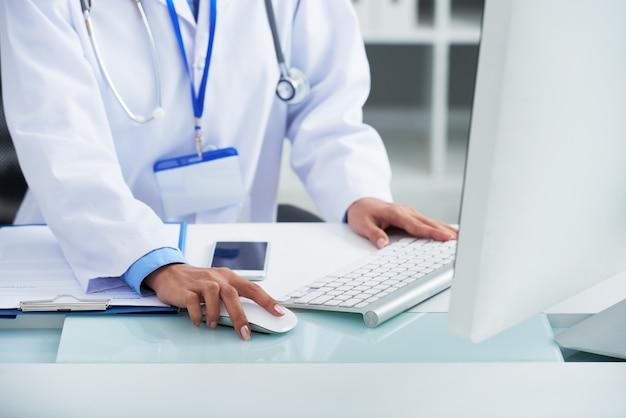 Médico irreconhecível no jaleco branco usando o computador no trabalho