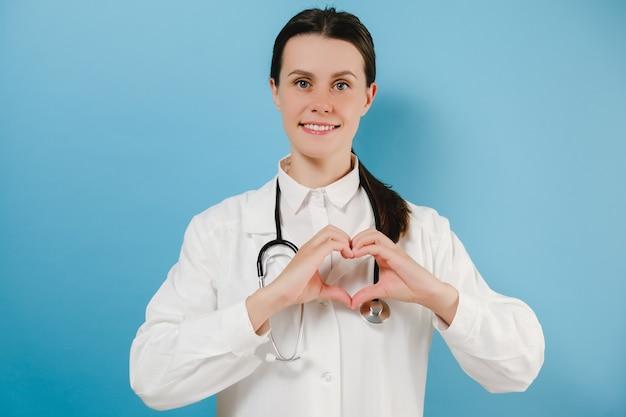 Médico jovem adorável mostrando o gesto do coração e sorrindo, cuidando de pacientes com amor, usa um estetoscópio de jaleco branco, modelos sobre a parede de fundo azul do estúdio. covid-19, conceito de pandemia
