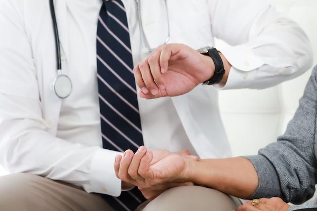 Médico jovem asiático falando com mulher idosa no hospital