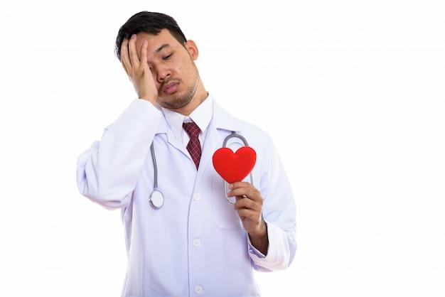 Médico jovem asiático segurando coração vermelho enquanto olha com sono