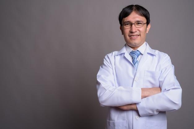 Médico jovem asiático usando óculos em um fundo cinza