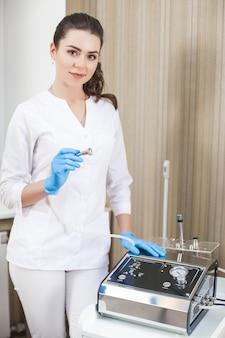 Médico jovem atraente com equipamento médico. cosmetologista feminina com aparelho dermatológico de microdermoabrasão. ferramenta de polimento
