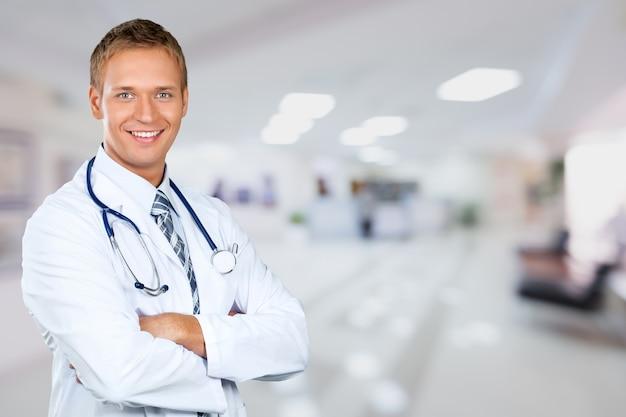 Médico jovem bonito com interior de hospital turva no fundo