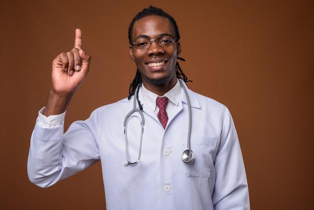 Médico jovem bonito homem africano contra fundo marrom