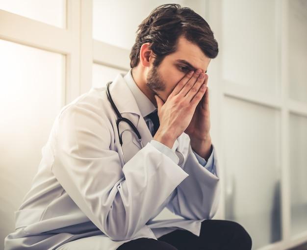 Médico jovem cansado no casaco branco está cobrindo seu rosto.