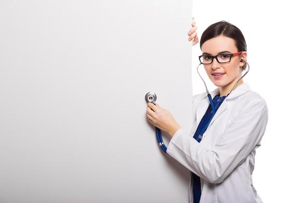 Médico jovem com estetoscópio e letreiro branco em branco como pano de fundo