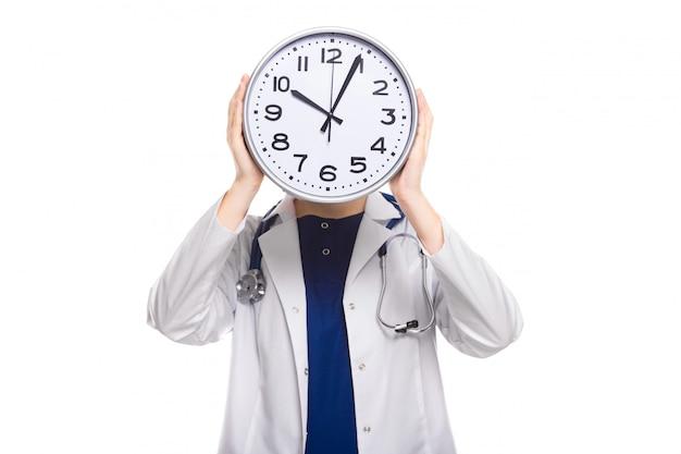 Médico jovem, com estetoscópio em apuros, segurando o relógio na frente da cabeça em uniforme branco