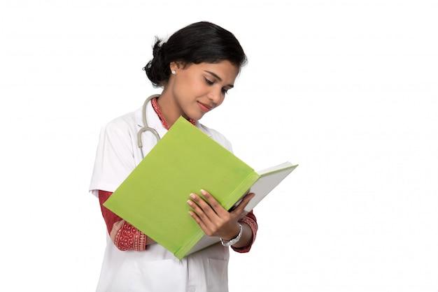 Médico jovem com estetoscópio está escrevendo no livro
