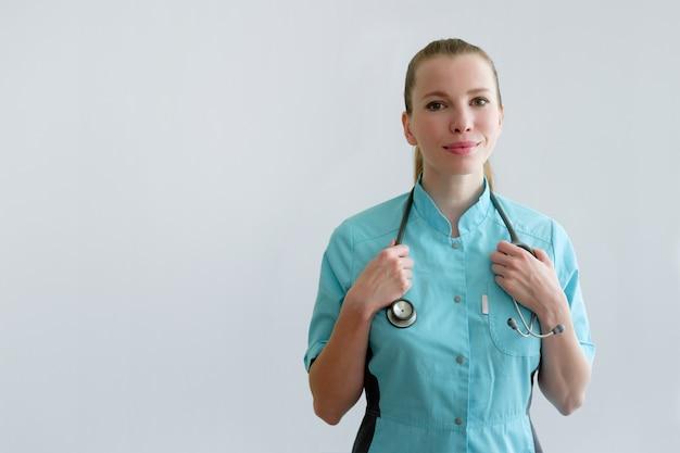 Médico jovem, com estetoscópio isolado em cinza