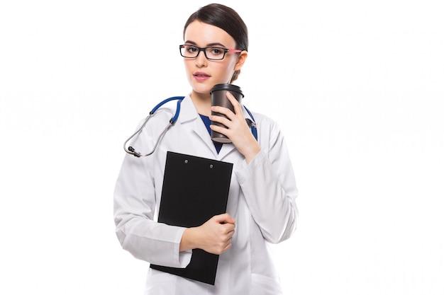 Médico jovem, com estetoscópio, segurando a área de transferência e café nas mãos em uniforme branco