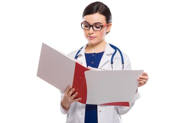 Médico jovem, com estetoscópio, segurando o fichário nas mãos em uniforme branco sobre branco