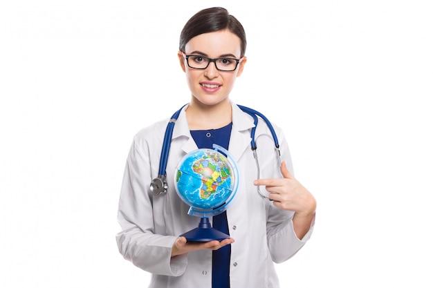 Médico jovem, com estetoscópio, segurando um globo do mundo nas mãos em uniforme branco