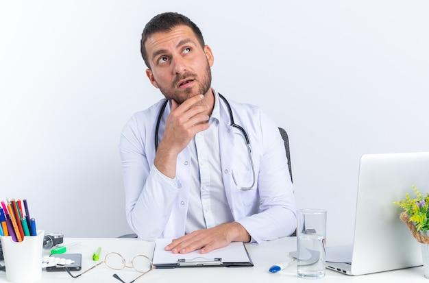 Médico jovem com jaleco branco e estetoscópio olhando para cima com a mão no queixo e expressão pensativa no rosto, sentado à mesa com laptop sobre fundo branco