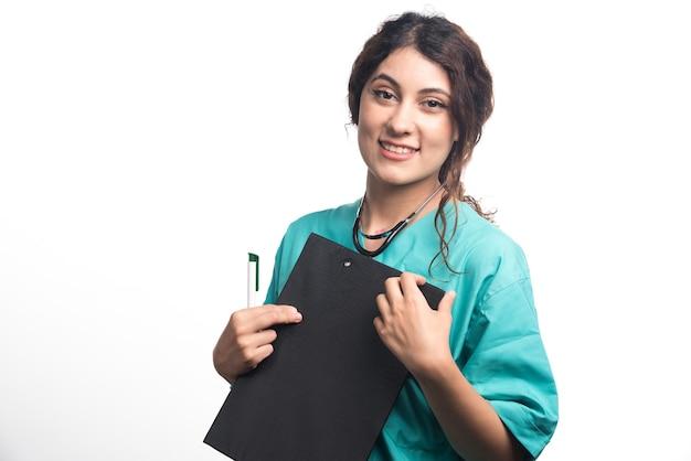 Médico jovem com prancheta, segurando a caneta na mão sobre fundo branco. foto de alta qualidade