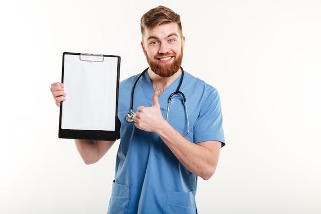 Médico jovem confiante segurando a prancheta e desistir de polegar