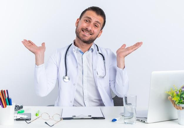 Médico jovem de jaleco branco e com estetoscópio olhando para frente feliz e alegre, sorrindo amplamente estendendo os braços para os lados, sentado à mesa com o laptop sobre a parede branca