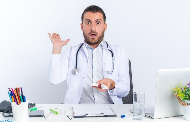 Médico jovem de jaleco branco e com estetoscópio segurando pílulas diferentes, espantado e surpreso, sentado à mesa com o laptop em branco