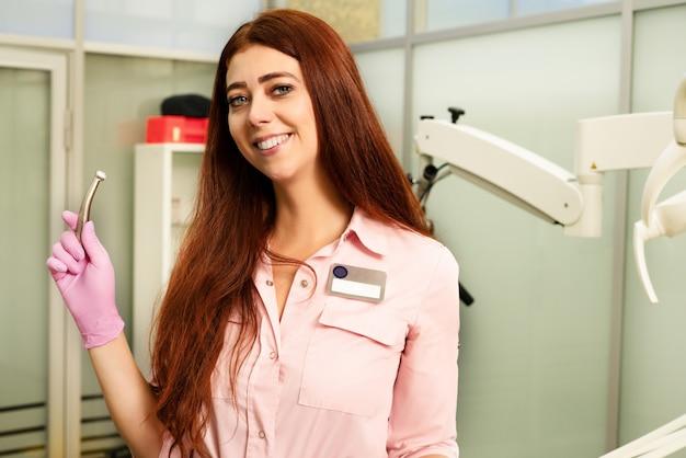 Médico jovem e bonita em roupas médicas e óculos de proteção, possui uma ferramenta dental profissional nas mãos
