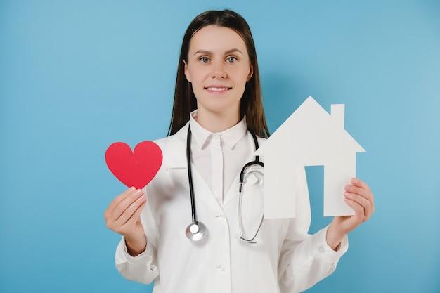 Médico jovem em uniforme médico profissional branco e estetoscópio segura uma pequena casa e um coração vermelho, feliz olhando para a câmera, posando sobre fundo azul do estúdio. cuidado, remédio, ajuda e suporte