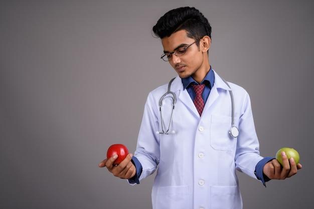 Médico jovem indiano na parede cinza