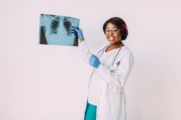 Médico jovem mulher afro-americana em roupas médicas, olhando para a imagem de raio-x