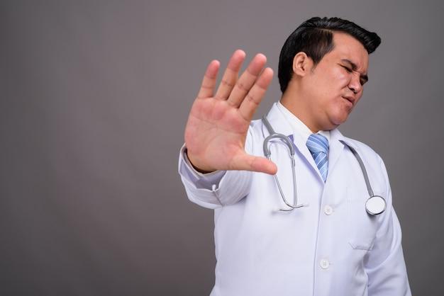 Médico jovem multi-étnica contra parede cinza