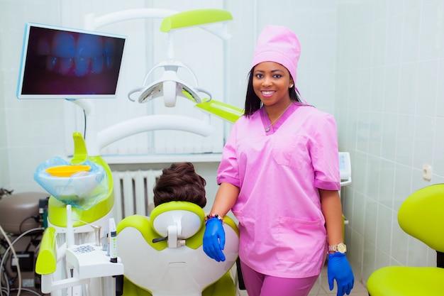 Médico jovem negra em uma clínica odontológica. o dentista se senta no armário ao lado da cadeira com o paciente