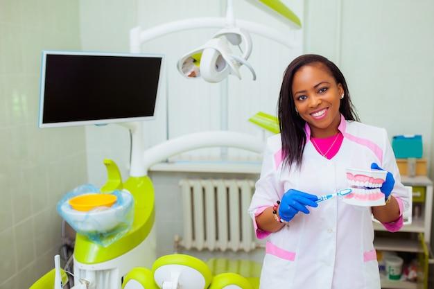 Médico jovem negra na clínica odontológica. o dentista está de pé com um boneco e falando sobre saúde. tecnologia médica
