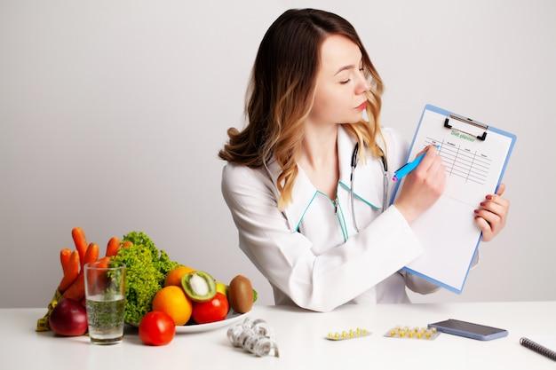 Médico jovem nutricionista na sala de consulta à mesa com frutas e legumes frescos, trabalhando em um plano de dieta
