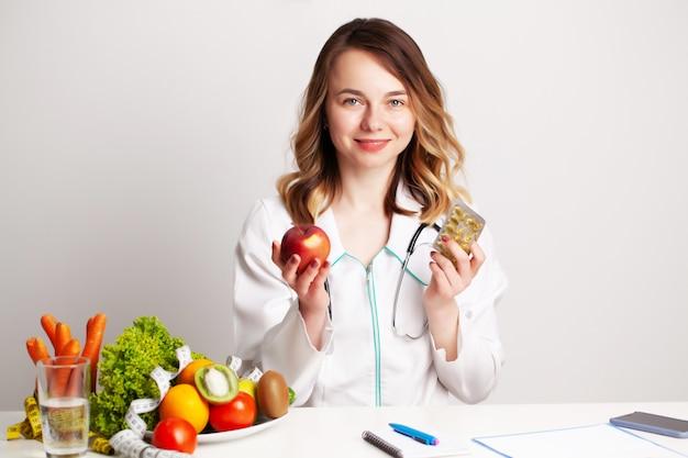 Médico jovem nutricionista na sala de consultoria na mesa com frutas e legumes frescos