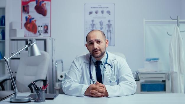Médico jovem praticante oferecendo aconselhamento médico online de seu escritório. médico usando tecnologia da internet para consultar pacientes durante a pandemia global covid-19. telemedicina e suporte de saúde.
