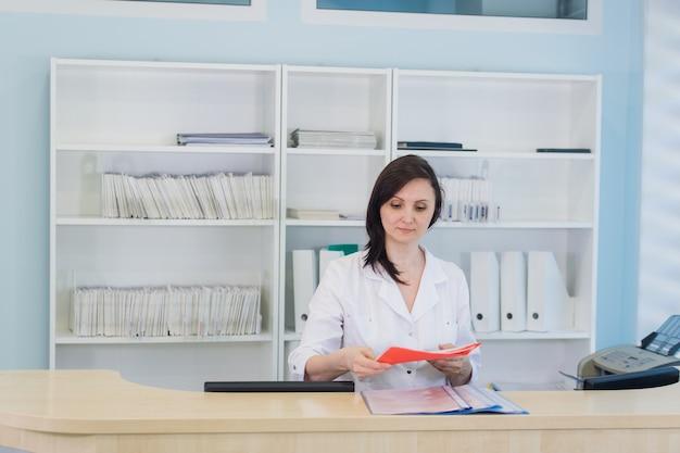 Médico jovem praticante, trabalhando na recepção da clínica, ela está atendendo telefonemas e agendando compromissos