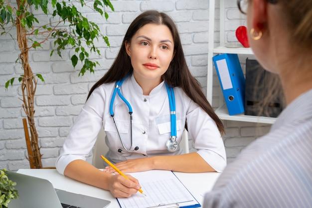 Médico jovem simpático, conversando com seu paciente no hospital