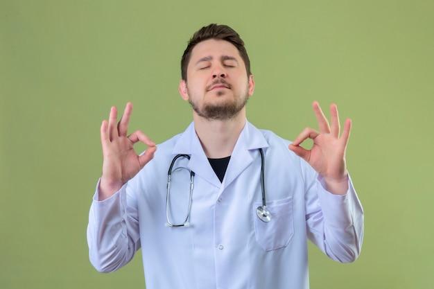 Médico jovem vestindo jaleco branco e estetoscópio olhando calmamente e feliz mostrando sinal de ok com os dedos