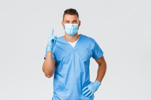Médico latino-americano bonito, enfermeiro na máscara médica e luvas, apontando o dedo para cima, fornecer informações importantes