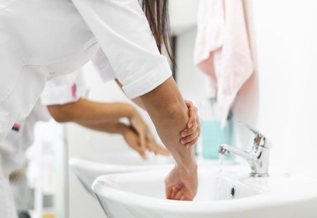 Médico lavando as mãos na clínica