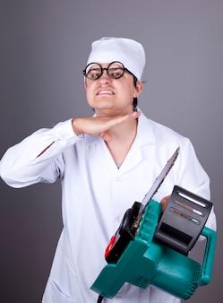 Médico louco com serra portátil.