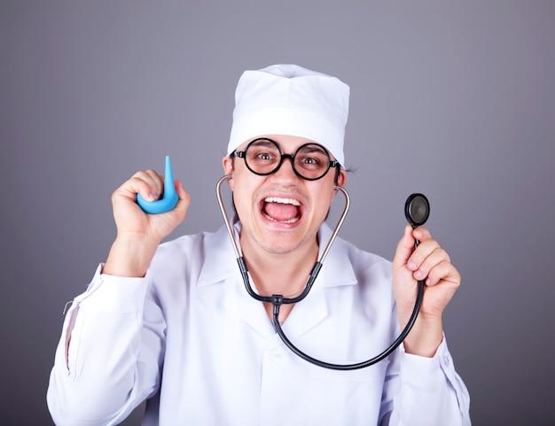 Médico louco com um estetoscópio e enema.