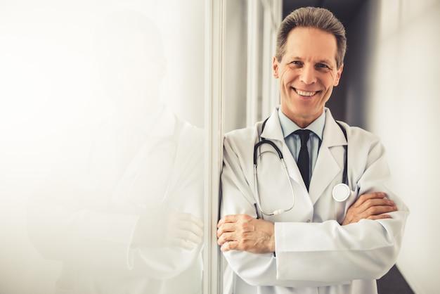 Médico maduro bonito no jaleco branco está olhando para a câmera.