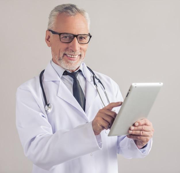 Médico maduro bonito no jaleco branco.