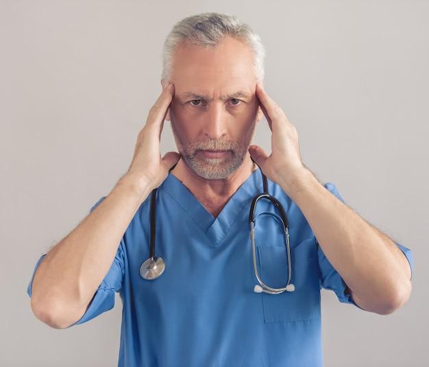 Médico maduro cansado no desgaste médico azul