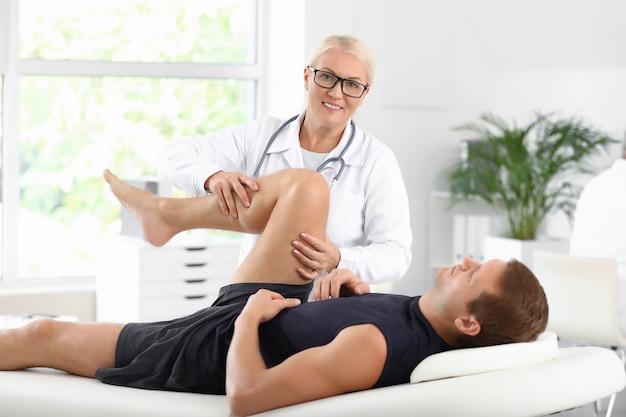 Médico maduro examinando esportista com dor nas articulações na clínica