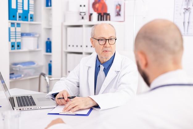 Médico maduro experiente, explicando o diagnóstico do paciente ao jovem médico durante a conferência. terapeuta especialista em clínica falando com colegas sobre doenças, profissional de medicina.