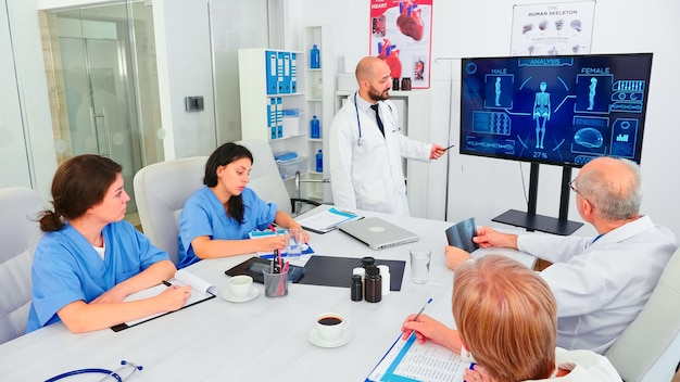 Médico maduro explicando o tratamento para enfermeiras durante o seminário de saúde apontando para o monitor digital. herapeuta clínica discutindo com colegas sobre doenças, profissional de medicina.
