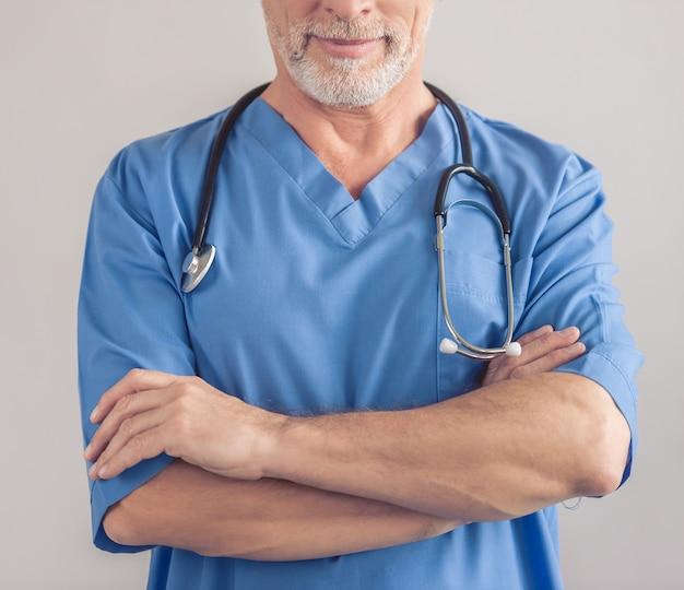 Médico maduro no desgaste médico azul.