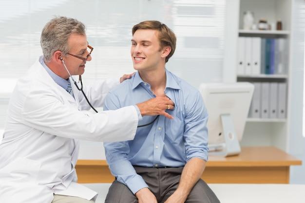 Médico maduro ouvindo seus pacientes felizes, peito com estetoscópio