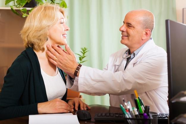 Médico maduro que verifica a tireóide de mulher sorridente