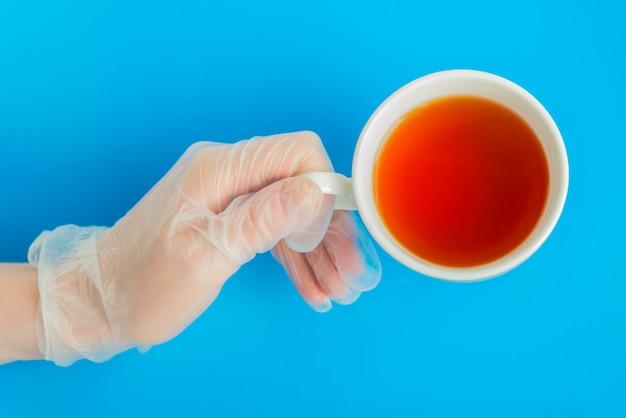 Médico mão na luva médica segura a xícara de chá branco sobre o fundo azul flatlay