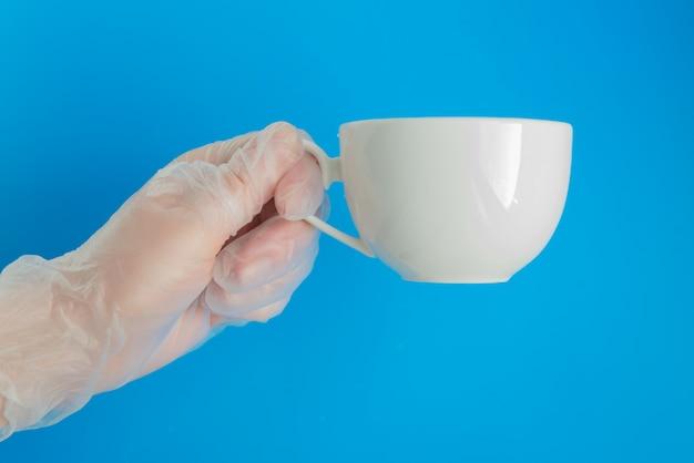 Médico mão na luva médica segura a xícara de chá branco sobre o fundo azul