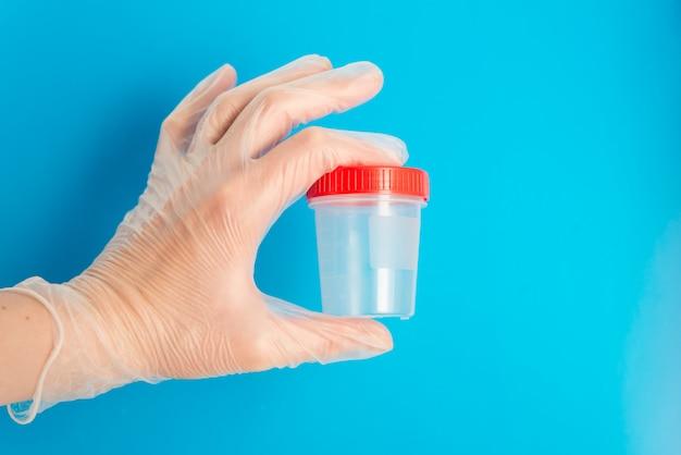 Médico mão na luva médica segura um recipiente de plástico vazio para testes em um fundo azul com espaço de cópia